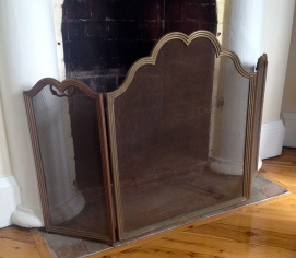 A small brass spark screen for the fireplace under restoration.